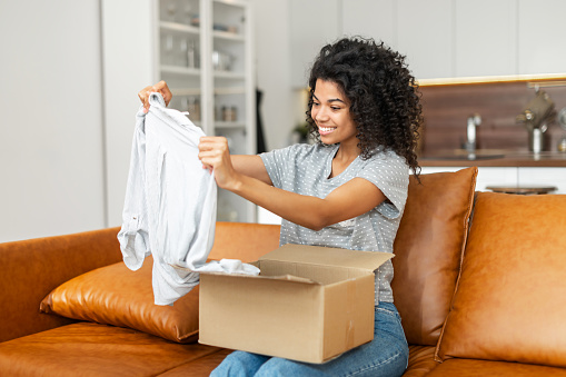 Satisfied smiling young African American woman sitting on the sofa opening parcel carton box, unpacking received gift, item from an online store, female customer happy with fast delivery and shipment