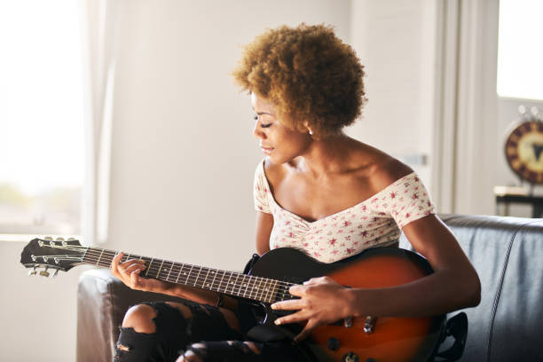 african american woman playing guitar at home stock photo