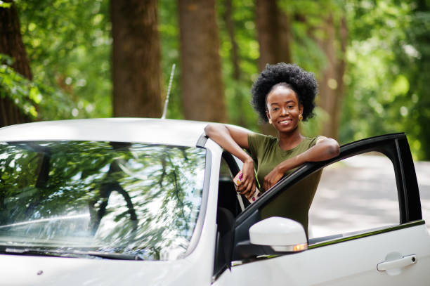 African american woman posed against white car stock photo