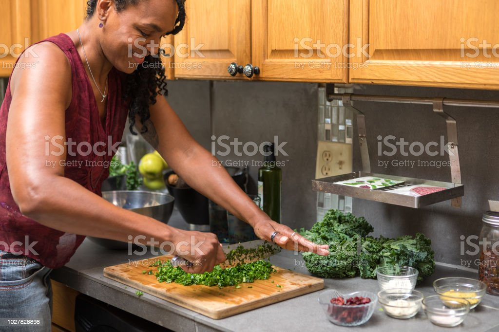 african american woman preparing kale salad stock photo