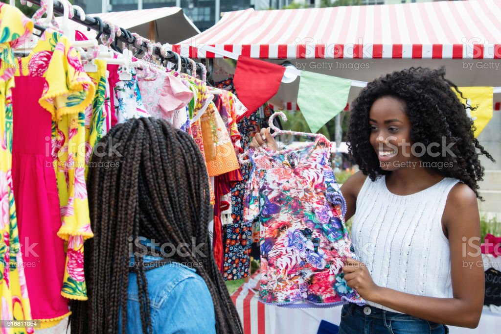 African american woman presenting colorful clothes outdoors at...