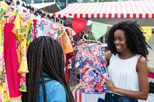 African american woman presenting colorful clothes at market African american woman presenting colorful clothes outdoors at typical traditional market market vendor stock pictures, royalty-free photos & images