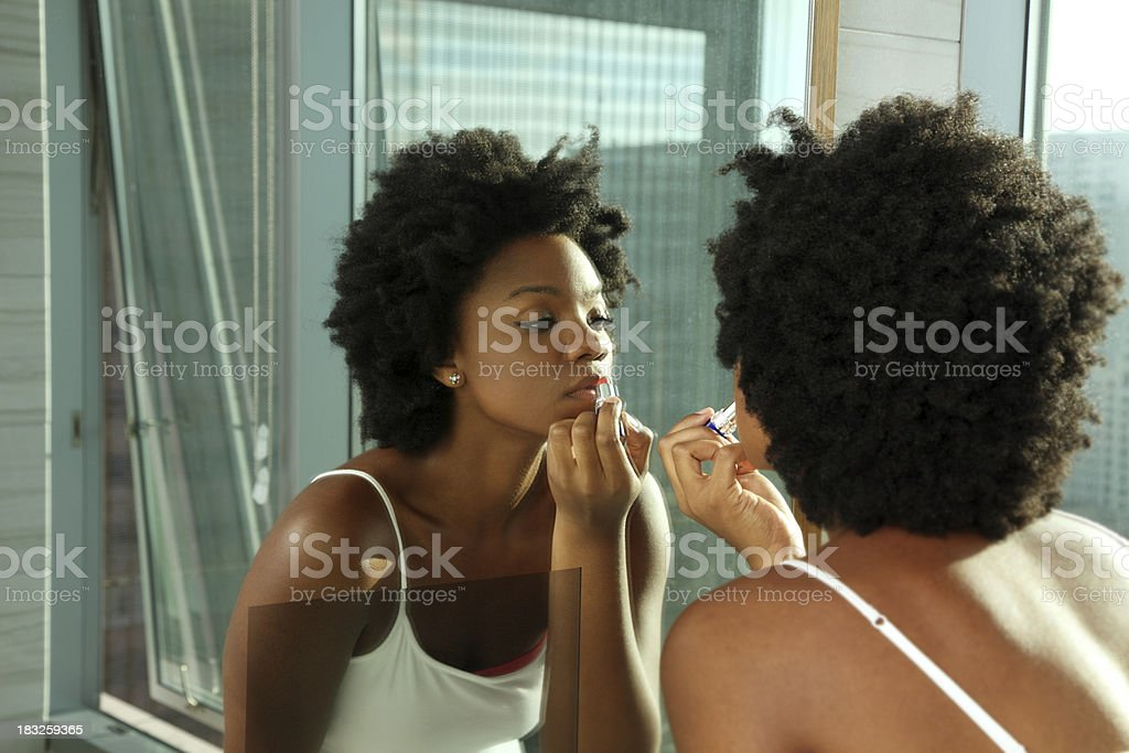 African American Woman Putting on Lipstick in a Mirror stock photo