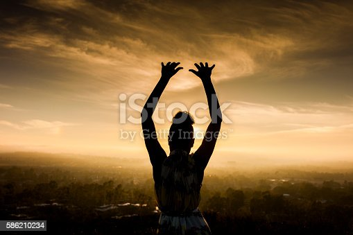 istock African American Woman Raising Arms at Sunset 586210234