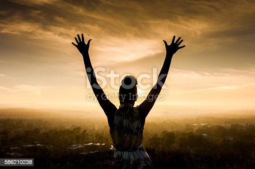 istock African American Woman Raising Arms at Sunset 586210238