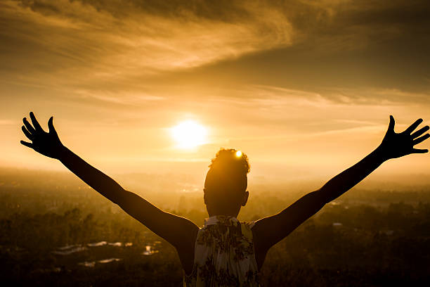 african american woman raising arms at sunset - praise and worship stock photos and pictures