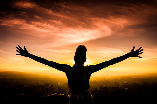 A young African American Woman raises her arms facing the sunset down over the valley and the ocean.