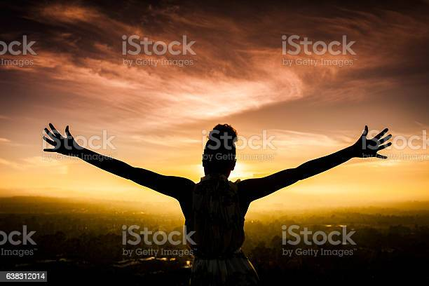 Photo of African American Woman Raising Arms at Sunset