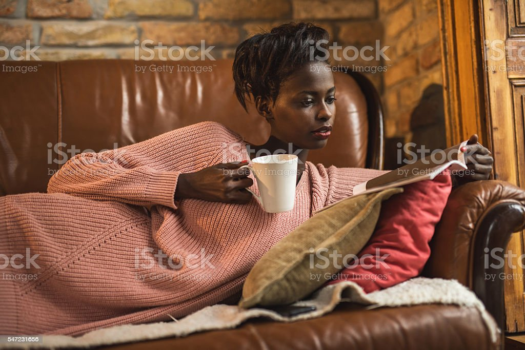 African American woman reading a magazine during coffee time.