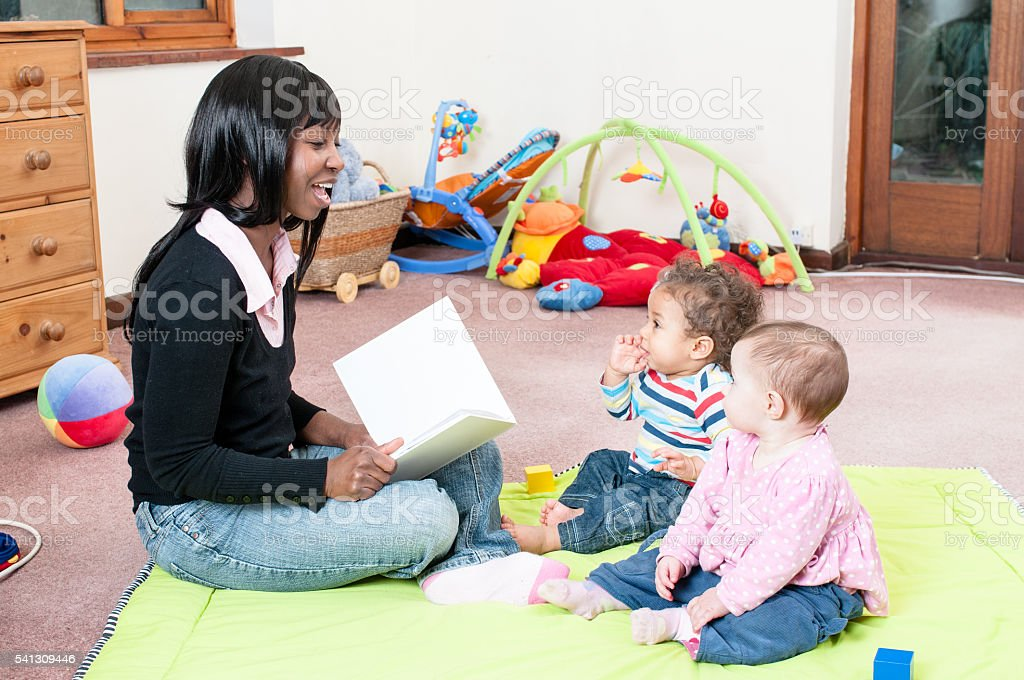 African American Woman Reading A Story To Group of Babies stock photo