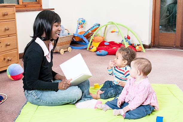 Afrikanische amerikanische Frau lesen eine Geschichte zu Gruppe von Babys – Foto