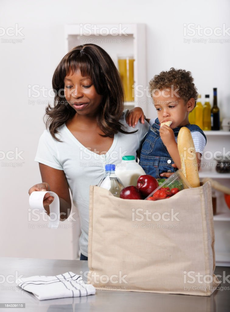 African American Woman Reviewing Receipt After Buying Groceries/ Shopping stock photo
