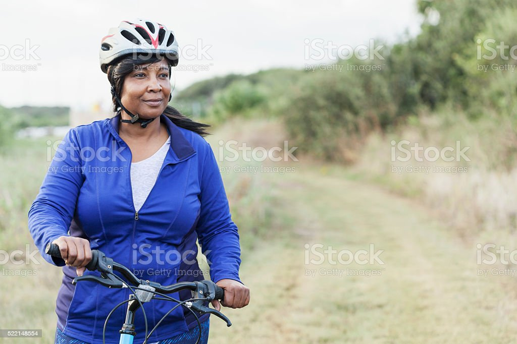 African American woman riding bike in park stock photo