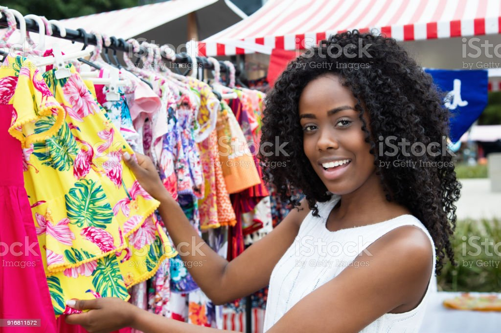 African american woman selling colorful clothes at market stock photo