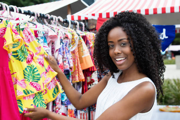 African american woman selling colorful clothes at market African american woman selling colorful clothes outdoors at typical traditional market market vendor stock pictures, royalty-free photos & images