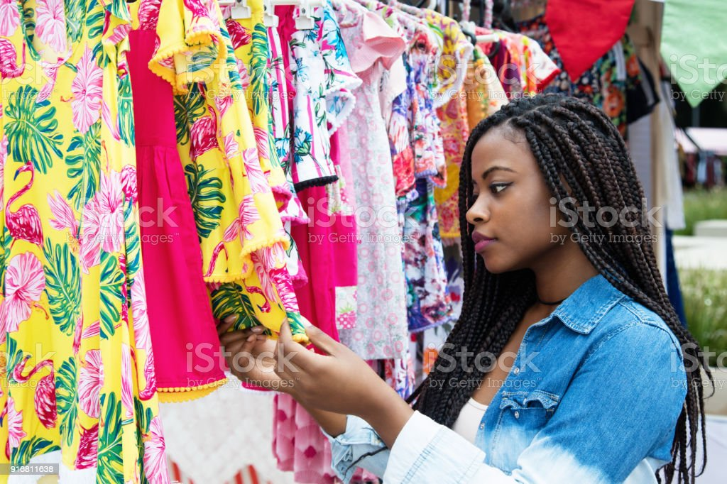 African american woman shopping colorful clothes outdoors at typical...