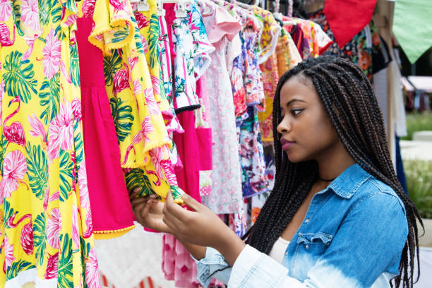 African american woman shopping colorful clothes at market stock photo