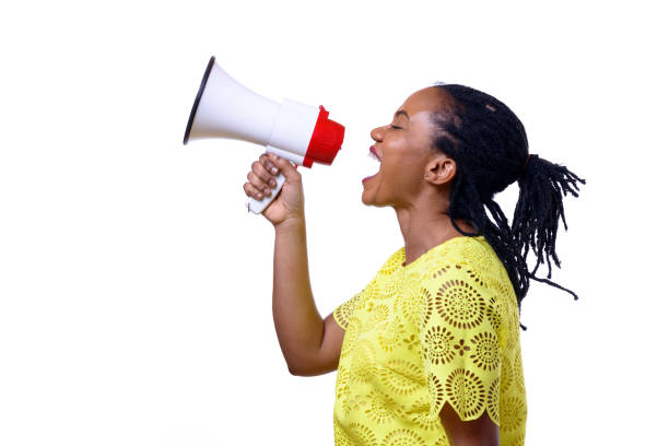 African American woman shouting at megaphone stock photo