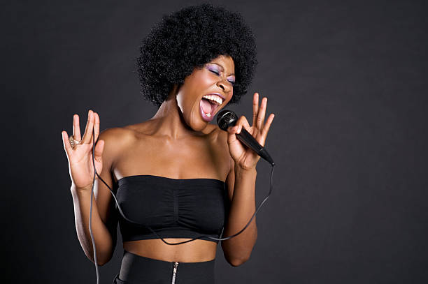 African American woman singing on microphone stock photo