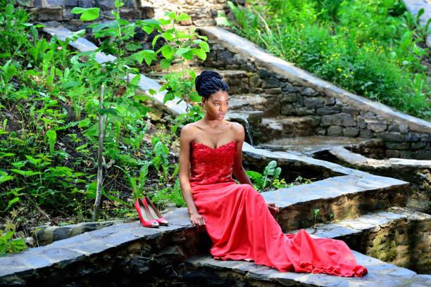 afroamerikanische frau sitzt im park posiert vor dem hintergrund der grünen pflanzen auf den felsen in einem roten kleid mit dreadlocks. - rote dreads stock-fotos und bilder