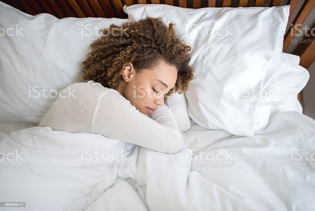 African American woman sleeping in bed stock photo