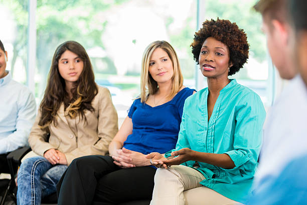 African American woman speaking during group therapy stock photo