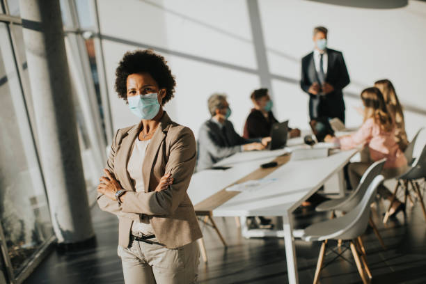 African American woman standing in office and wear mask as protection from corona virus stock photo