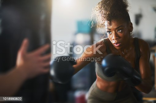 istock african american woman striking punching bag in home gym 1018990622