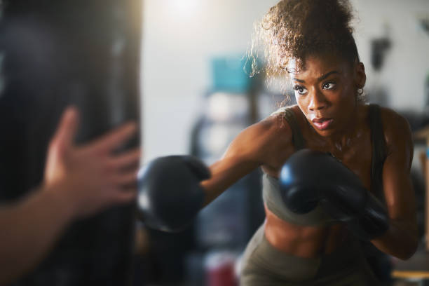 african american woman striking punching bag in home gym - boxing stock pictures, royalty-free photos & images