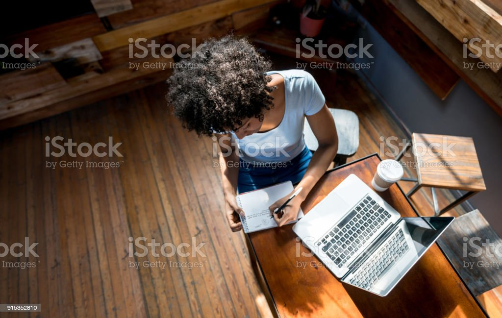 African american woman studying online and taking notes on a notepad