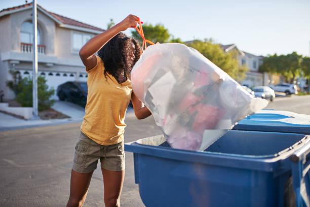 african american woman taking out the tash in las vegas neighborhood stock photo