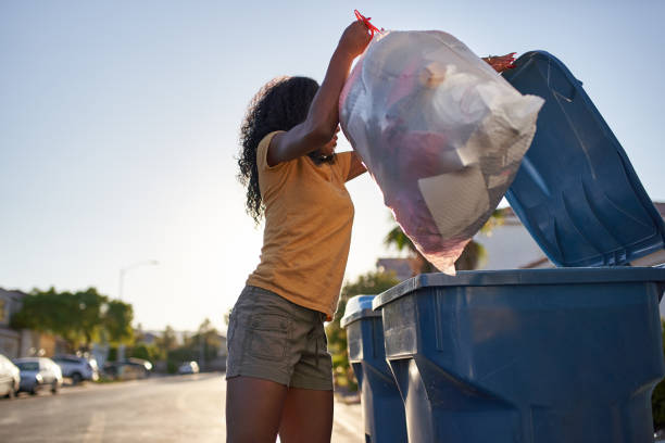 african american woman taking out the trash in las vegas neighborhood stock photo