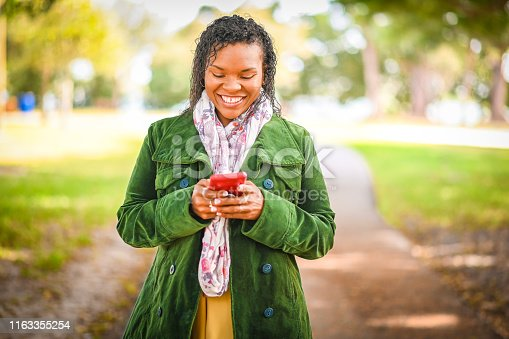 A woman uses a cell phone in a public park or outdoor area wearing a light fall or spring jacket and scarf. She is a pretty African American woman in her 30's. She is cheerful and candid using a smart phone to text or answer emails
