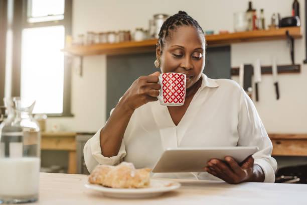 Afroamerikanische Frau mit einem Tablet über Frühstück zu Hause – Foto
