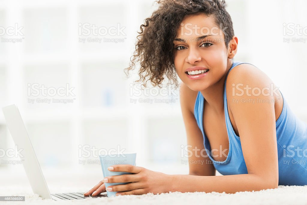 African American woman using computer while lying on carpet. royalty-free stock photo
