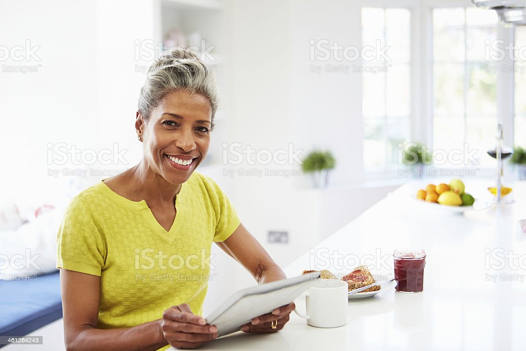 African American Woman Using Digital Tablet At Home stock photo