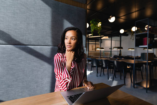 African American woman using her laptop and thoughful stock photo