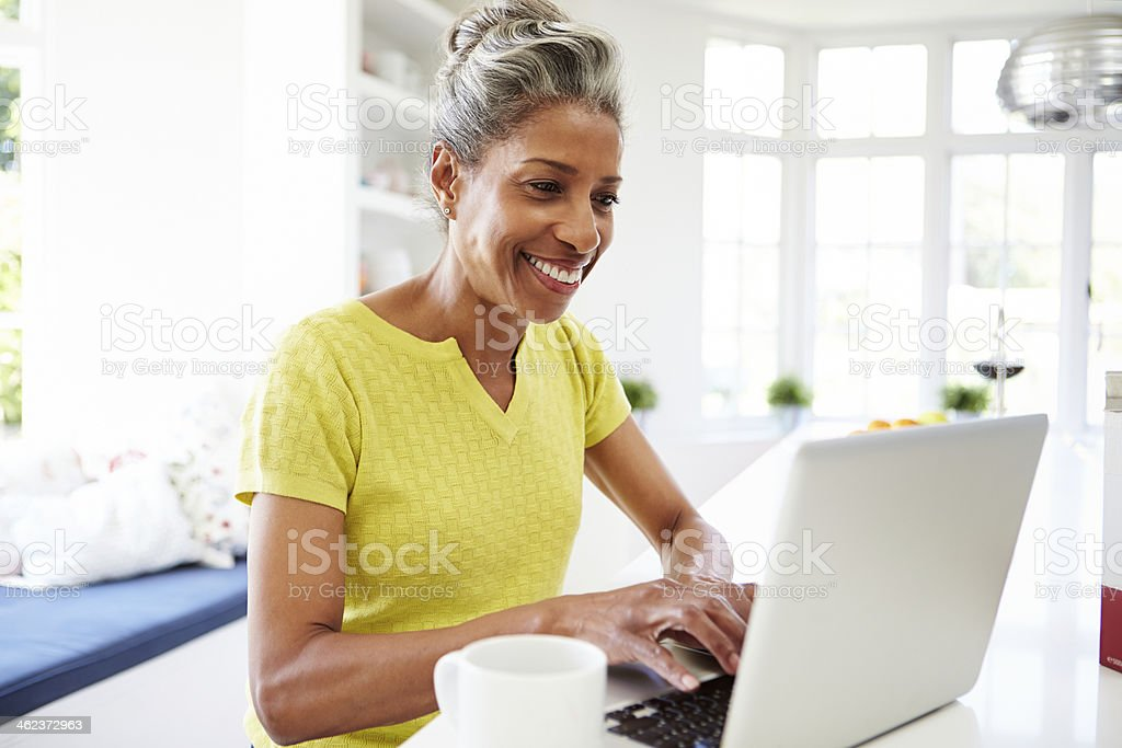 African American Woman Using Laptop In Kitchen At Home stock photo