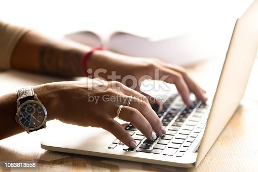 African American woman using laptop, typing on keyboard, chatting in social networks, girl writing post, report, message, female student working on project, searching online, hands view close up