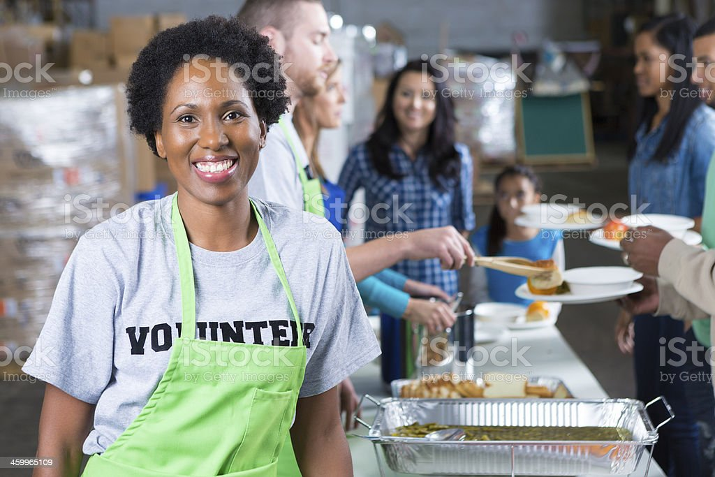 African American woman volunteering at community soup kitchen stock photo