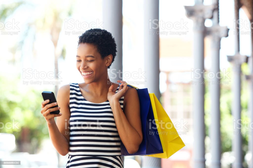 african american woman walking with cellphone and shopping bags stock photo