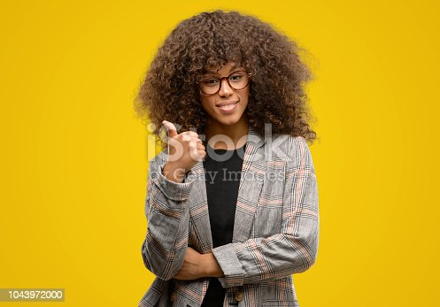African american woman wearing a jacket happy with big smile doing ok sign, thumb up with fingers, excellent sign