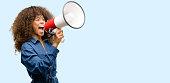 istock African american woman wearing blue jumpsuit communicates shouting loud holding a megaphone, expressing success and positive concept, idea for marketing or sales 1043969226