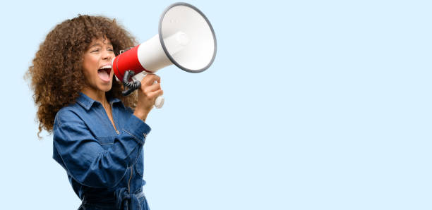 African american woman wearing blue jumpsuit communicates shouting loud holding a megaphone, expressing success and positive concept, idea for marketing or sales African american woman wearing blue jumpsuit communicates shouting loud holding a megaphone, expressing success and positive concept, idea for marketing or sales crying stock pictures, royalty-free photos & images