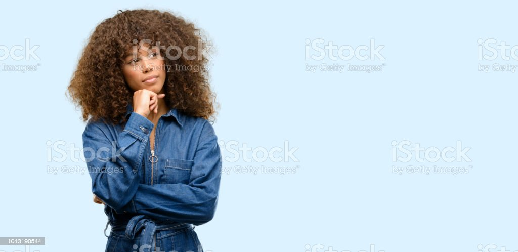 African american woman wearing blue jumpsuit thinking and looking up expressing doubt and wonder stock photo