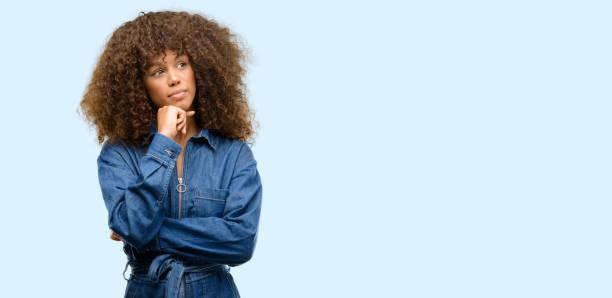 afroamerikanische frau tragen blaue overalls denken und äußern zweifel und wunder nachschlagen - jeans overall stock-fotos und bilder