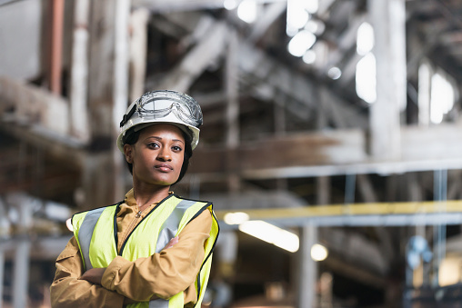 Portrait of a confident, young African American woman working in a manufacturing plant.  She is standing with arms folded, looking at the camera, in a storage facility or warehouse.  She is wearing a white hardhat and yellow safety vest.