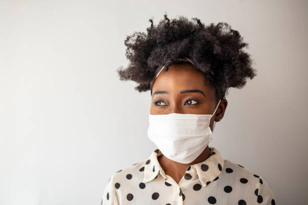 African - American woman wearing mask for protect. Stop the virus and epidemic diseases. Healthy woman in blue medical protective mask. Health protection and prevention during flu and infectious outbreak. pollution mask stock pictures, royalty-free photos & images