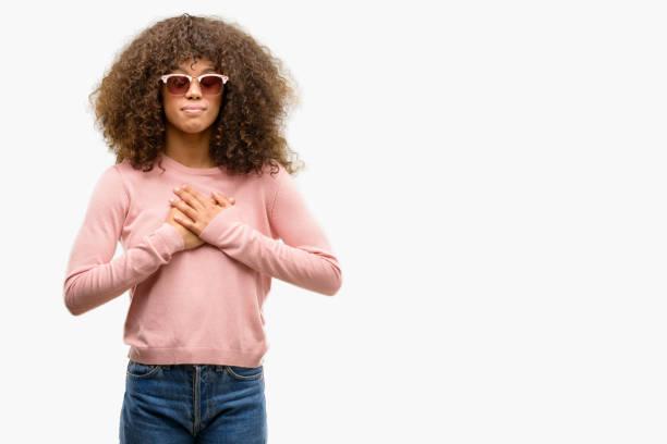 afroamerikanische frau rosa sonnenbrille lächelnd mit hände auf die brust mit geschlossenen augen und dankbar geste auf gesicht. gesundheitskonzept. - die wahrheit tut weh stock-fotos und bilder