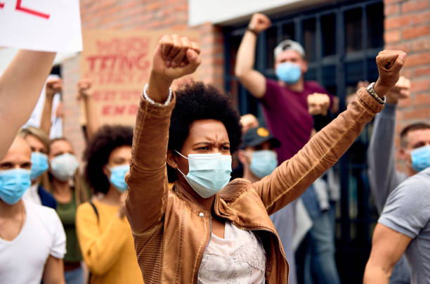 african american woman wearing protective face mask while protesting with arms raised on city streets. - protestor stock pictures, royalty-free photos & images